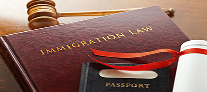 Leather bound Immigration Law book with gold embossed type with a judges gavel, legal document and a passport.